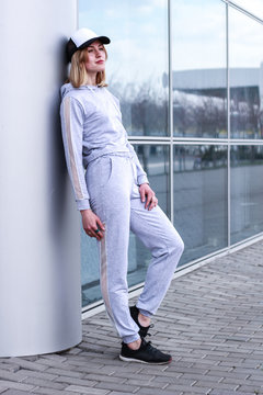 The girl is blonde in a gray sports suit. Street clothing. Sport. Advertising. Fashion and style. Trends. Mockup. Copyspace