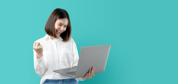 Young Asian woman smiling holding laptop computer with fist hand and excited for success on light blue background.