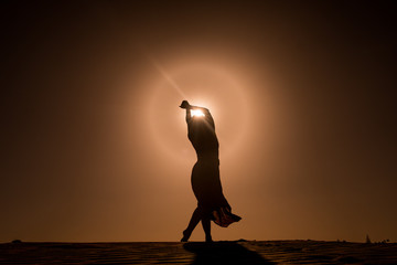silhouette of young woman with long skirt dancing in evocative and magic way on top of desert dune at sunset with sun high in the sky