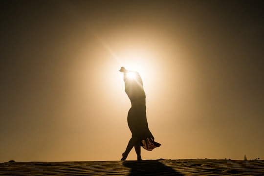 silhouette of young woman with long skirt dancing in evocative and confident way on top of desert dune at sunset with sun high in the sky