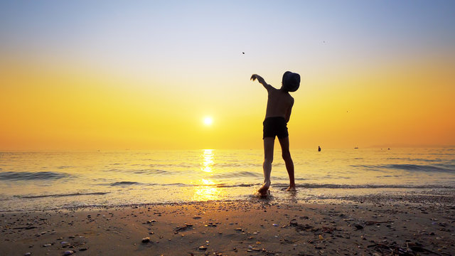 Silhouette of boy with hat throwing stones skipping on sea water surface. Summer vacation concept with vibrant orange sky