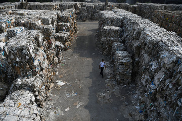 A security officer walks past piles of paper waste, imported by a paper factory, in Mojokerto