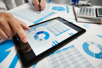 Obraz Businessman working and calculating, reads and writes reports. Using tablet pc. Office employee, table closeup. Business financial accounting concept. - fototapety do salonu