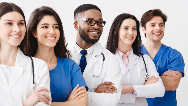 Happy Medical Staff Standing Together In Clinic