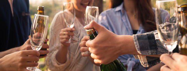 Hands of man in group of friends opening champange for celebrate, cropped dimension for banner