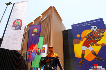 """An employee walks in front of a picture of Egyptian mascot for the Africa Cup of Nations, named """"TUT"""" at the Cairo International Stadium ahead of the Africa Cup of Nations opening soccer match between Egypt and Zimbabwe in Cairo"""