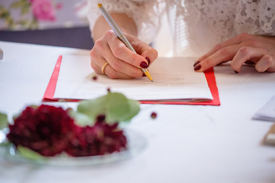 Bride signing marriage license or wedding contract during wedding celebration