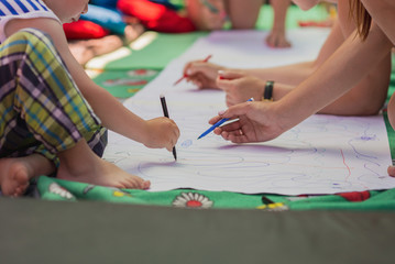 Children and adults paint together on a large white canvas on the floor.
