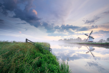 Wall Mural - Dutch windmill by river at misty sunrise