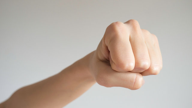 Woman's fist isolated on a light gray background. Close up to the camera. Front view.
