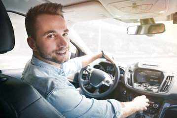 Young male driver behind the wheel Wall mural