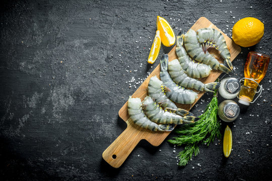 Raw shrimps on a cutting Board with lemon slices, spices and dill.