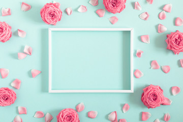 Beautiful flowers composition. Blank frame for text, pink rose flowers on pastel mint background. Valentines Day, Easter, Birthday, Mother's day. Flat lay, top view, copy space