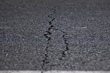 An image of gray asphalt road split by a crack. A metaphor concept for an age crisis, broken dreams, psychological break, marriage relationship problems, shattered trust