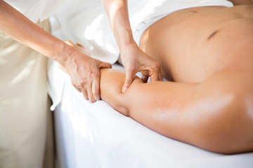 Asian man laying on bed for herb compress and pampering thai massage therapist, relaxation and wellness lifestyle.
