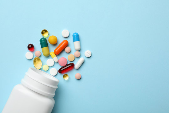 Bottle and scattered pills on color background, top view. Space for text
