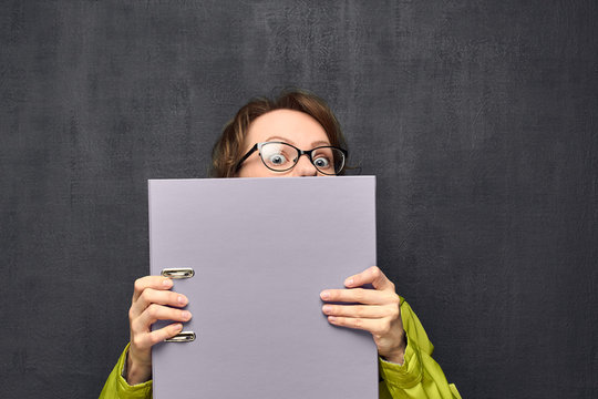 Portrait of afraid girl looking out from big folder