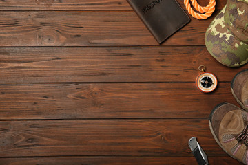 Flat lay composition with camping equipment on wooden background. Space for text