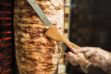 Cooking shawarma and ciabatta in a cafe. A man in disposable gloves cuts meat on a skewer.