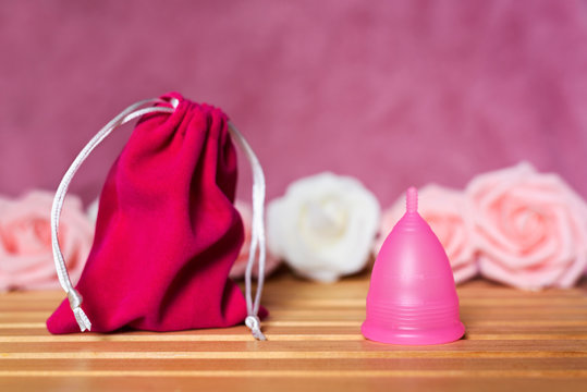 Pink sack bag and menstrual cup from medicinal silicone. Pink and white roses. Concept of zero waste alternative for popular intimate hygiene products for period.