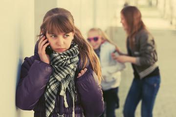 Teen girl calling on cell phone on city street