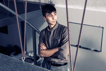 Young handsome business man standing on stair in office