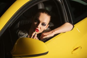 Young stylish fashion woman sitting in a car