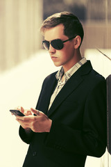 Young business man in sunglasses using smart phone on city street