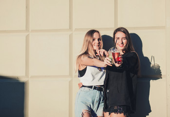 Two young beautiful smiling hipster girls in trendy summer hipster clothes holding drinks