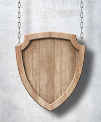 Defense protection shield shaped sign made of bright wood and hanging on chains with concrete wall background