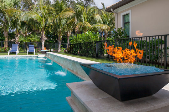 Gas fire pit next to a pool with waterfall