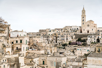Long panoramic views of the rocky old town of Matera with its stone roofs.