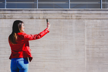 Millenial woman taking a selfie with happy gesture to pretend to be successful in life.