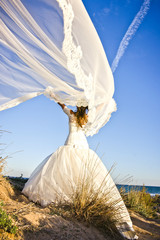 Happy bride with her wedding dress blowing her veil to the wind on the beach.