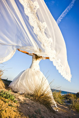 Wedding veil flying in the wind held by the newly married woman while strolling in the sun on the beach.