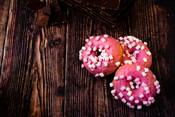 Aged wooden table with delicious pink donuts for lunch tasty sweets for young people, copy space.