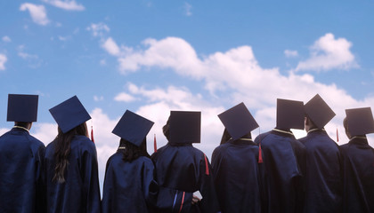 group of graduates in graduation cap and gown in front of building
