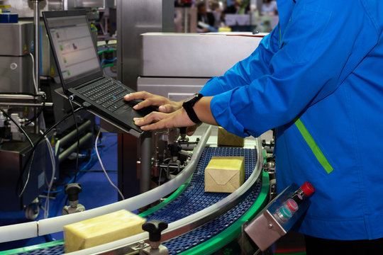 manufacturing engineer used computer to control product inspection system automation machine in modern factory while products are moving on the conveyor belt to warehouse for logistic transport.