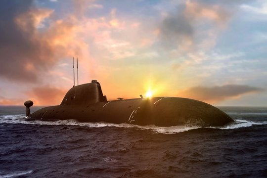 Naval submarine at sea surface during sunset