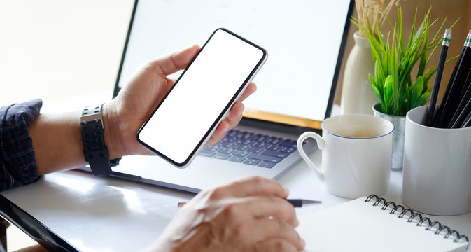 Man using mobile phone and laptop on workspace