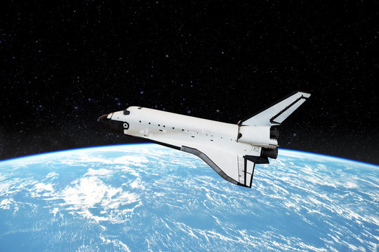 Space shuttle orbiting in  a space over the earth planet and starry background. Elements of this image furnished by NASA.