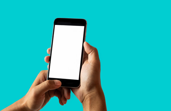 Hand holding white mobile phone with blank white screen Dark Turquoise background.