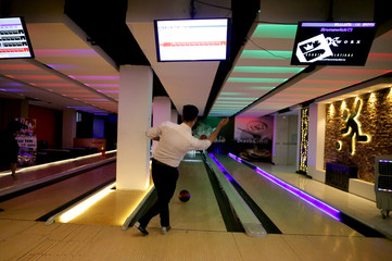 A man throws a ball at Bravo Bowling Alley in Kabul