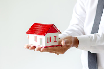 Business young man holding house, Real estate investment is a business to build a house to sell to...