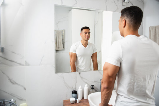 Back side of smiling young man looking at mirror