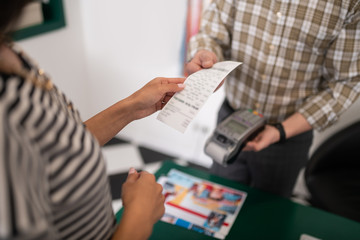 Close-up photo of seller handing the receipt to the customer