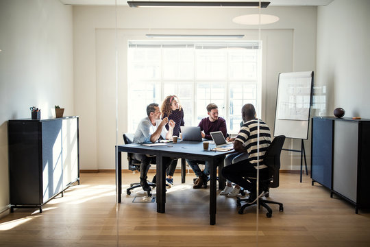 Diverse group of designers meeting together around an office tab