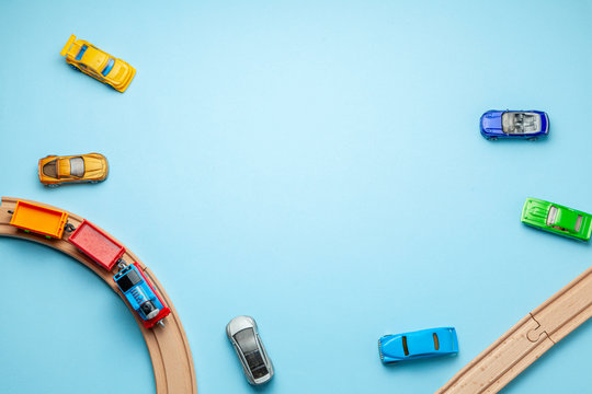 Children's railway with wooden rails and cars on a blue background, top view. Copy space for text.