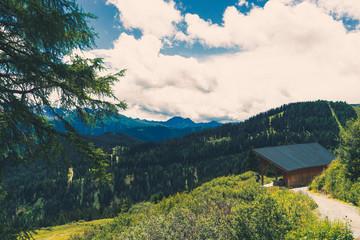 Berg Landschaft in den Tiroler Alpen in Österreich mit dramatischen Himmel. Überall Bäume und Berggipfel. Ein schwermütiger Himmel im Hintergrund. Ein Wanderweg und eine Hütte mit Wanderer.