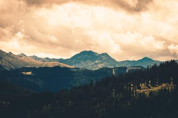 Stimmungsvolle Berg Landscahft in den Tiroler Alpen in Österreich. Die Farben sind dunkel und mystisch. Der Nadelwald und die Berggipfel dominieren das Bild unter einem gefährlichen Himmel.